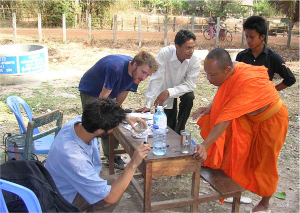 Water testing Ang Village. Arsenic contamination of wells is a problem in Cambodia. Visiting students from Marlboro College work with Rith, head monk at Ang Pagoda and others in the village to use a water testing kit. Our dug wells were found to be free of arsenic.